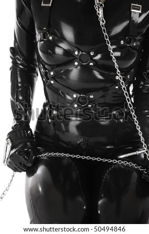 Torso of woman in black latex catsuit and body harness with chain - stock photo