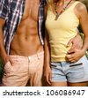Torso of young embracing couple at summertime. - stock photo