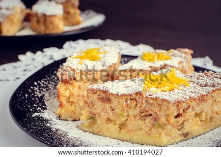 Torta di riso - classical Italian dessert. Rice cake with almonds, candied orange peels and amaretto. Delicious puffed rice pie. A slices of rice cake in a plate. Italian food. Selective focus. - stock photo