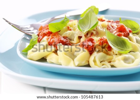 Tortellini with tomato sauce and cheese, fresh basil - stock photo