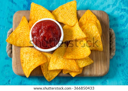 tortilla chips and tomato dip on wooden surface - stock photo