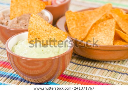 Tortilla Chips & Dips - Mexican totopos with guacamole, refried beans and salsa.  - stock photo