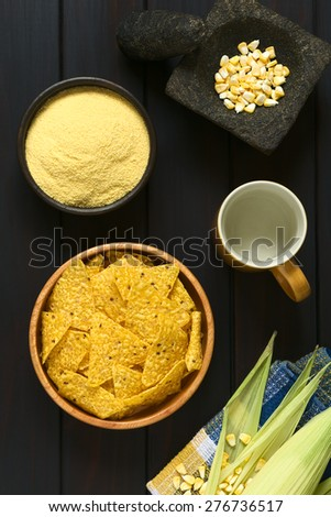 Tortilla chips in wooden bowl surrounded by its ingredients water, cornmeal and corn, photographed overhead on dark wood with natural light - stock photo