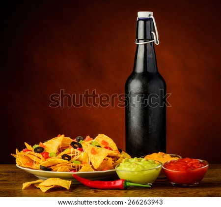 tortilla chips with cheese, salsa and guacamole dip and bottle of beer - stock photo