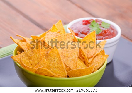 Tortilla chips with spicy tomato salsa with jalapeno - stock photo