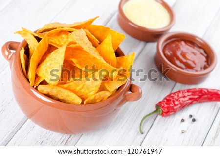 Tortilla chips with two different dips on a white table - stock photo