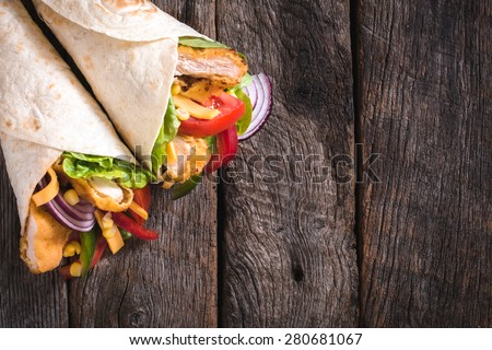 Tortilla sandwiches with fried chicken and vegetables on wooden background with blank space  - stock photo