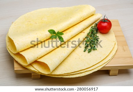 Tortilla stack with herbs on the wood background - stock photo