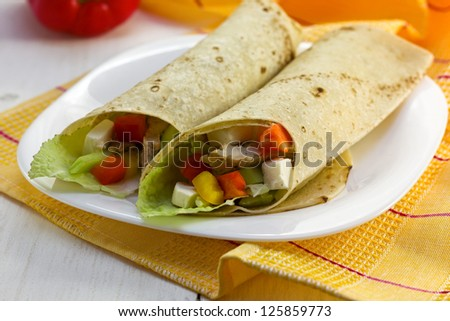 tortilla with chicken and vegetables on a white plate - stock photo