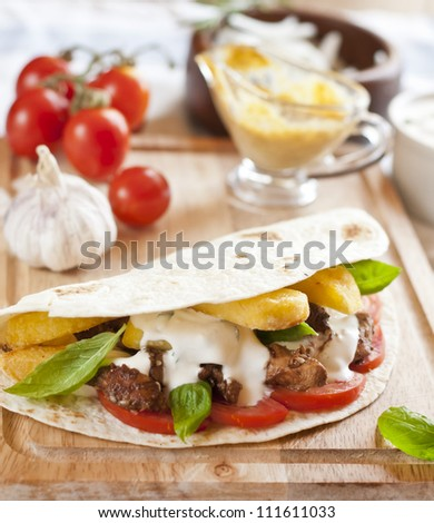 tortilla with chicken meat, fries and basil - stock photo