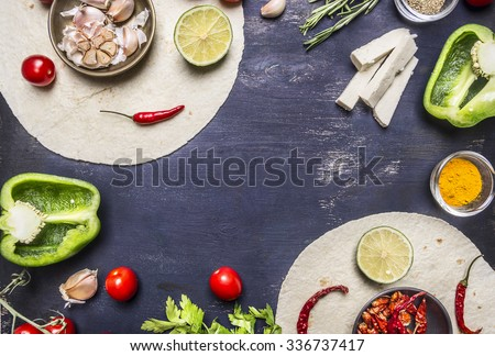tortilla with Ingredients for cooking vegetarian burrito with vegetables and lime on wooden rustic background top view close up  with text area - stock photo