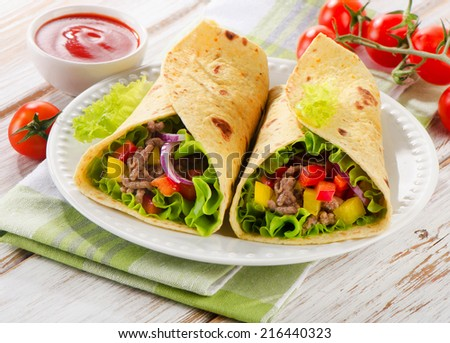 tortilla wraps with meat and fresh vegetables on white plate. Selective focus - stock photo