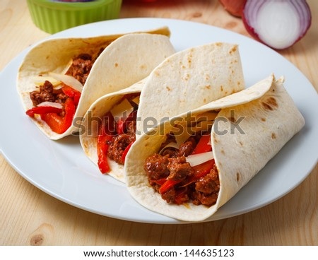 tortillas filled with  with beef meat, pepperoni, onions, cheese and tomato sauce - stock photo