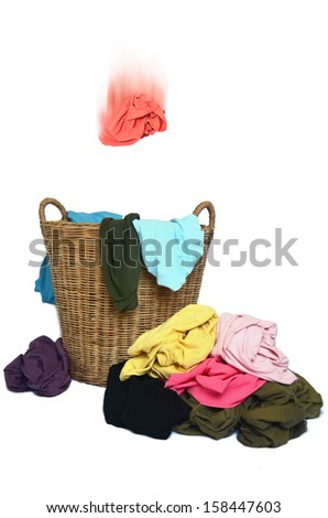 Toss shirt in wicker basket and  pile of colorful shirts  - stock photo