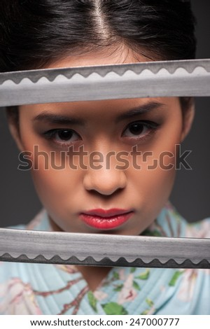 Total concentration. Young beautiful Japanese woman looking aggressively through two katana swords while standing against grey background - stock photo