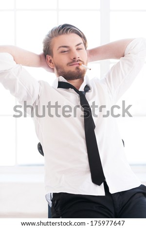Total relaxation. Handsome young man in shirt and tie holding head in hands while sitting on the chair - stock photo