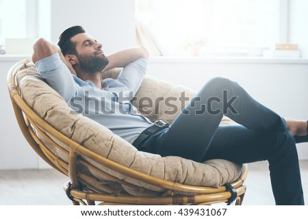Total relaxation. Handsome young man keeping eyes closed and holding hands behind head while sitting in big comfortable chair at home   - stock photo