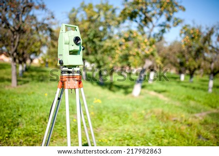 Total station surveying and measuring engineering equipment at work in garden or forest - stock photo
