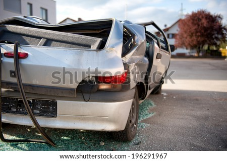 Totaled hatchback motor vehicle after a smash viewed from behind showing a flattened roof and shattered windows as though it rolled over with glass shards underneath and bent and buckled bodywork - stock photo