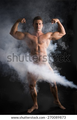 Totally naked male bodybuilder with smoke hiding genitalia, looking at camera, on dark background - stock photo