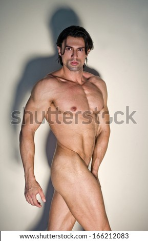 Totally naked muscular man on neutral background looking at camera - stock photo