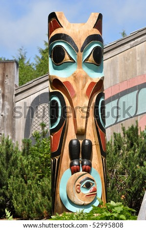 totem in front of tribal lodge - stock photo