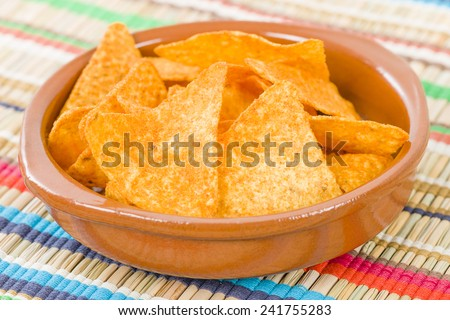 Totopos - Mexican tortilla chips on a colourful background.  - stock photo