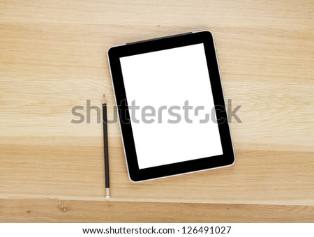 Touch screen tablet computer with blank screen and pencil on wooden table - stock photo