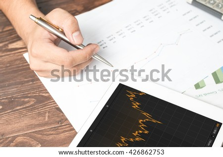 Touching stock market graph on a touch screen device. Trading on stock market concept. Closeup photo. - stock photo