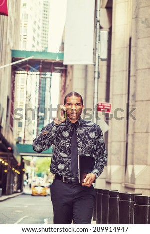 Tough African American businessman in New York. Wearing flower patterned shirt, tie, carrying laptop computer, young guy walking on street, talking on phone. Yellow cab on background. Instagram effect - stock photo