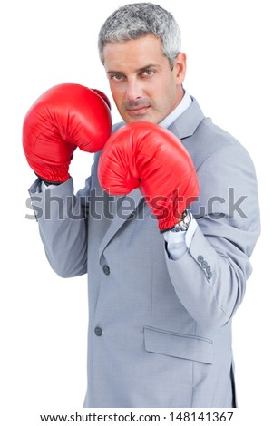 Tough businessman with boxing gloves on white background - stock photo