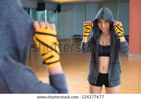 Tough female boxer enjoying her reflection in the gym mirror - stock photo