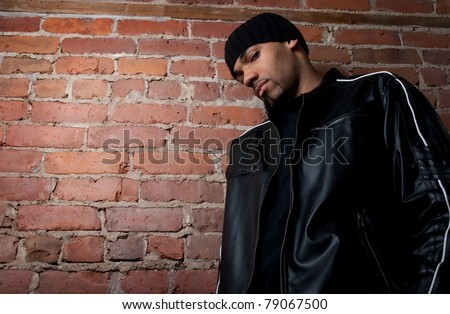 Tough guy dressed in black near a brick wall. - stock photo