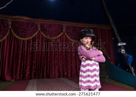 Tough Looking Girl Wearing Combat Helmet and Striped Dress Standing Confidently with Arms Crossed on Stage with Red Curtain - stock photo