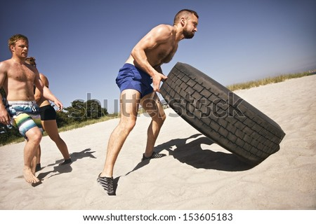 Tough male athlete flipping a truck tire. Young people doing  exercise on beach. - stock photo