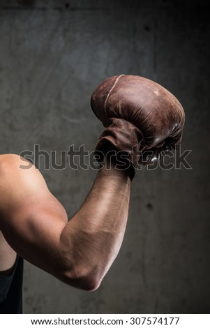 Tough male's hand in vintage boxing glove - stock photo