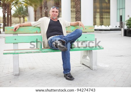 Tough man relaxing on a bus bench - stock photo
