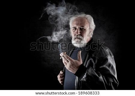 Tough man with white beard smoking - stock photo