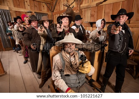 Tough men and women pull out their weapons in a saloon - stock photo