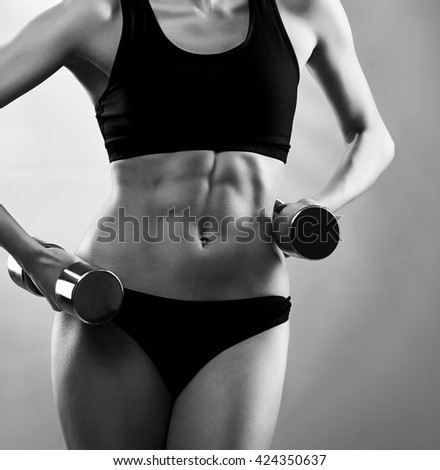 Tough personality. Cropped closeup of a perfect muscular toned abs of a fitness woman at the studio black and white shot - stock photo