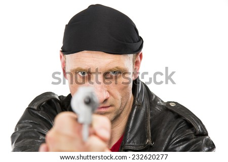 Tough white guy dressed in all in black with a red t shirt underneath a leather jacket and black bandana on his head, holding out a pistol in a gangster pose directly to the front - stock photo