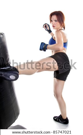 Tough woman kickboxer practicing boxing with a punching bag. - stock photo