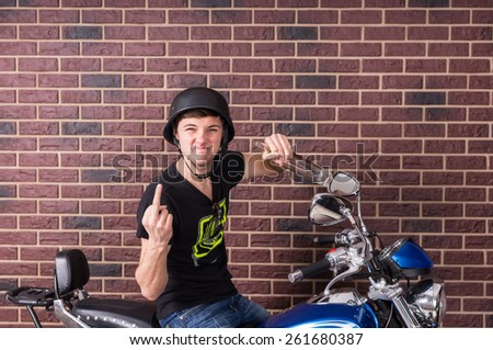 Tough Young Rebellious Man Wearing Helmet and Giving the Finger to Camera while Sitting on Motorcycle in front of Brick Wall - stock photo