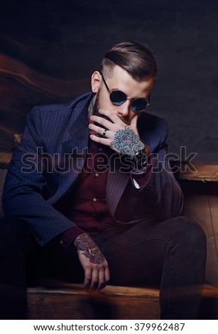 Toughtful man in sunglasses with tattoo on his arm. - stock photo