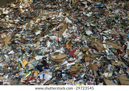 TOULOUSE, FRANCE - CIRCA 2008: Newspapers and plastic bottles lie in a heap at an undisclosed recycling facility circa 2008 in Toulouse. The paper and plastic will be sorted and baled. - stock photo