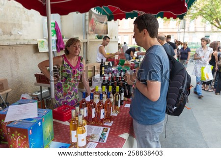 TOULOUSE, FRANCE - JULY 27, 2014: A vendor selling wine at the March Saint Aubin, the Saint Aubin Market, in Toulouse. Marche Saint Aubin is only held on Sundays. - stock photo