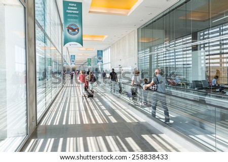 TOULOUSE, FRANCE - JULY 27, 2014: Passengers on their way to their gate at Toulouse-Blagnac airport in Toulouse, France. In 2012, the Toulouse airport served 7,559,350 passengers. - stock photo