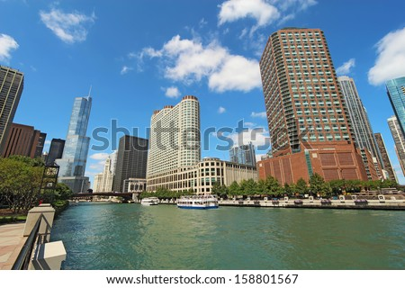 Tour boats and the city skyline along the Chicago River in Chicago, Illinois against a bright blue sky with white clouds - stock photo