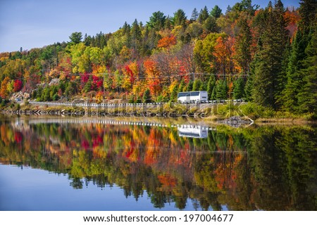 Tour bus driving though fall forest with colorful autumn leaves reflecting in lake. Highway 60 at Lake of Two Rivers, Algonquin Park, Ontario, Canada. - stock photo