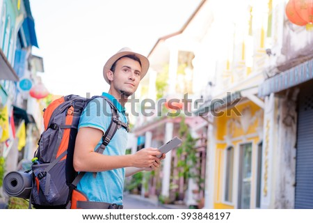 Tourism and technology. Concept of online map. Traveling backpacker young man using digital tablet  outdoor. - stock photo